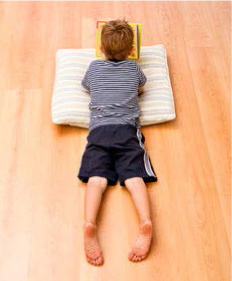 boy reading on hardwood floor